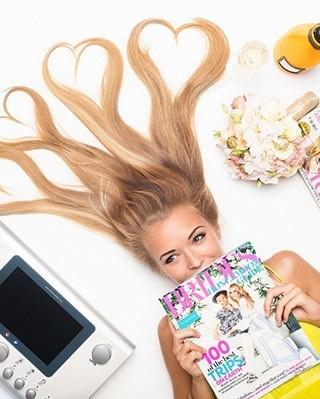 Fiatal lány fekszik magazinnal a kezében egy EMS készülék mellett
